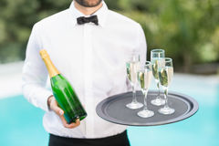 Waiter holding champagne flutes and bottle. Midsection of waiter holding champagne flutes and bottle at poolside Royalty Free Stock Images