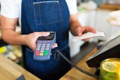 Waiter holding credit card reader Royalty Free Stock Image