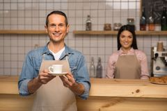 Waiter holding cup of coffee. And looking at the camera with waitress on the background Stock Image