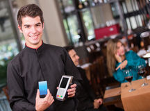 Waiter holding a dataphone Stock Photos