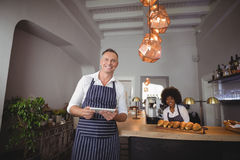 Waiter holding digital tablet while waitress smiling in background at counter Royalty Free Stock Photo