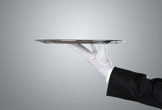 Waiter holding empty silver tray. Over gray background with copy space royalty free stock photography