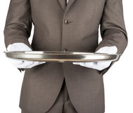 Waiter holding empty silver tray. Over white background royalty free stock image