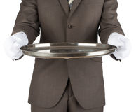 Waiter holding empty silver tray. Over white background stock photo