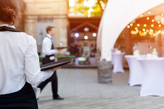 Waiter holding an empty tray in outdoor cafe. Catering service. royalty free stock images