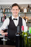 Waiter holding a glass of wine Royalty Free Stock Images