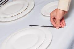 Waiter is holding knife Stock Image
