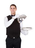 Waiter holding lid cover over empty tray Royalty Free Stock Images