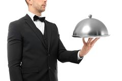 Waiter holding metal tray with cover on white background. Close up view Royalty Free Stock Photos