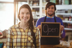 Waiter holding open signboard and standing with customer Stock Photos