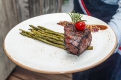 Waiter Holding A Plate with Filet Mignon. And Asparagus stock photo
