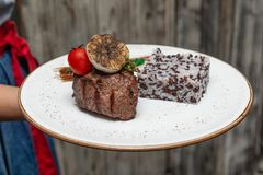 Waiter Holding A Plate with Filet Mignon and Rice Mix. And Half Garlic Decoration royalty free stock photo