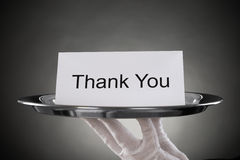 Waiter Holding Plate With The Text Thank You On Paper. Close-up Of Waiter Holding Plate With The Text Thank You On Paper royalty free stock photography