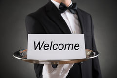 Waiter Holding Plate With Welcome Text On Paper. Close-up Of Waiter Holding Plate With Welcome Text On Paper Royalty Free Stock Images