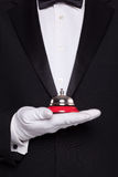 Waiter holding a service bell. Waiter in black tie and white gloves holding a service bell Royalty Free Stock Photos