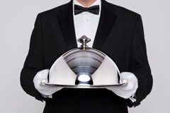 Waiter holding a silver cloche. Waiter serving a meal under a silver cloche or dome Stock Photo