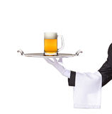 Waiter holding a silver tray with a beer on it. Waiter holding a silver tray with a beer mug on it stock images
