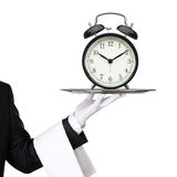 Waiter holding silver tray with a clock Stock Photos