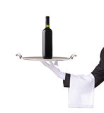 Waiter holding a silver tray with a red wine. On it Stock Photo
