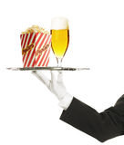 Waiter holding a tray with a beer glass and popcor Royalty Free Stock Photos