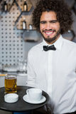 Waiter holding tray of beer glass and tea cup Stock Images