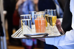 Waiter holding a tray with beverages during cocktail party. Waiter holding a tray with champagne glasses and other beverages during a cocktail event stock photography