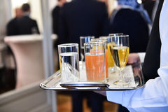 Waiter holding a tray with beverages during cocktail party. Waiter holding a tray with champagne glasses and other beverages during a cocktail event royalty free stock image