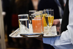 Waiter holding a tray with beverages during cocktail party. Waiter holding a tray with champagne glasses and other beverages during a cocktail event royalty free stock photos