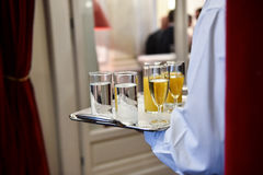 Waiter holding a tray with beverages during cocktail party. Waiter holding a tray with champagne glasses and other beverages during a cocktail event stock image