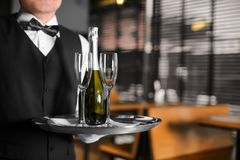 Waiter holding tray with bottle of champagne. And glasses indoors Stock Photography