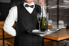 Waiter holding tray with bottle of champagne. And glasses indoors Stock Photo