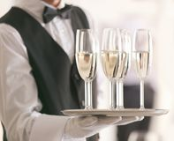 Waiter holding tray with champagne on blurred background, stock photography