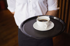 Waiter holding tray with coffee cup. In a bar stock photo
