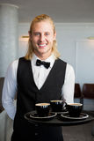 Waiter holding a tray with coffee cups in restaurant Royalty Free Stock Image