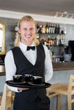 Waiter holding a tray with coffee cups in restaurant Royalty Free Stock Images