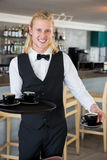 Waiter holding a tray with coffee cups in restaurant Stock Photography