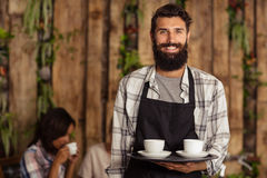 Waiter holding a tray with coffees. In the bar Royalty Free Stock Photos