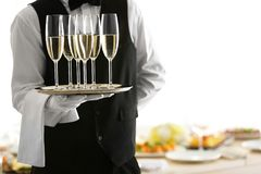 Waiter holding tray with glasses on blurred background. Waiter holding tray with glasses of champagne on blurred background, close up view Royalty Free Stock Photos