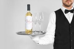 Waiter holding tray with glasses and bottle of wine on light background. Young waiter holding tray with glasses and bottle of wine on light background Royalty Free Stock Photo