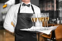Waiter holding tray with glasses of champagne. Indoors Royalty Free Stock Image