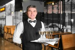 Waiter holding tray with glasses of champagne. Indoors Royalty Free Stock Photography