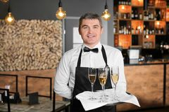 Waiter holding tray with glasses of champagne. Indoors Stock Images