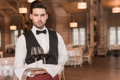 Waiter holding tray with wineglasses. Waiter holding tray with glasses with red wine and looking at camera Royalty Free Stock Photography
