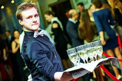 Waiter holding a tray with glasses of vine. Catering or celebration concept. male waiter holding a tray with glasses of vine at party, Authentic shot in mixed Royalty Free Stock Photography