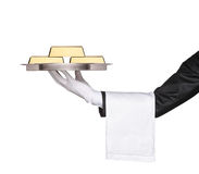 A waiter holding a tray with gold bars on it Royalty Free Stock Photos