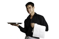 Waiter holding Tray Out. A waiter holding out a tray in one hand and a towel on the other Royalty Free Stock Image