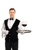 Waiter holding a tray with red wine Royalty Free Stock Photos