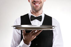 Waiter holding tray. Smiling butler. Isolated over white background Stock Photos