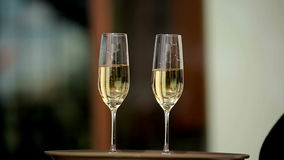 Waiter holding a tray of two glasses with champagne shows visitors. Close up. Waiter holding a tray of two glasses with champagne shows visitors. Close up shot stock video footage