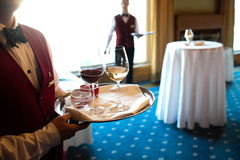 A waiter holding a tray. With white and red wine glasses for serving Stock Photography